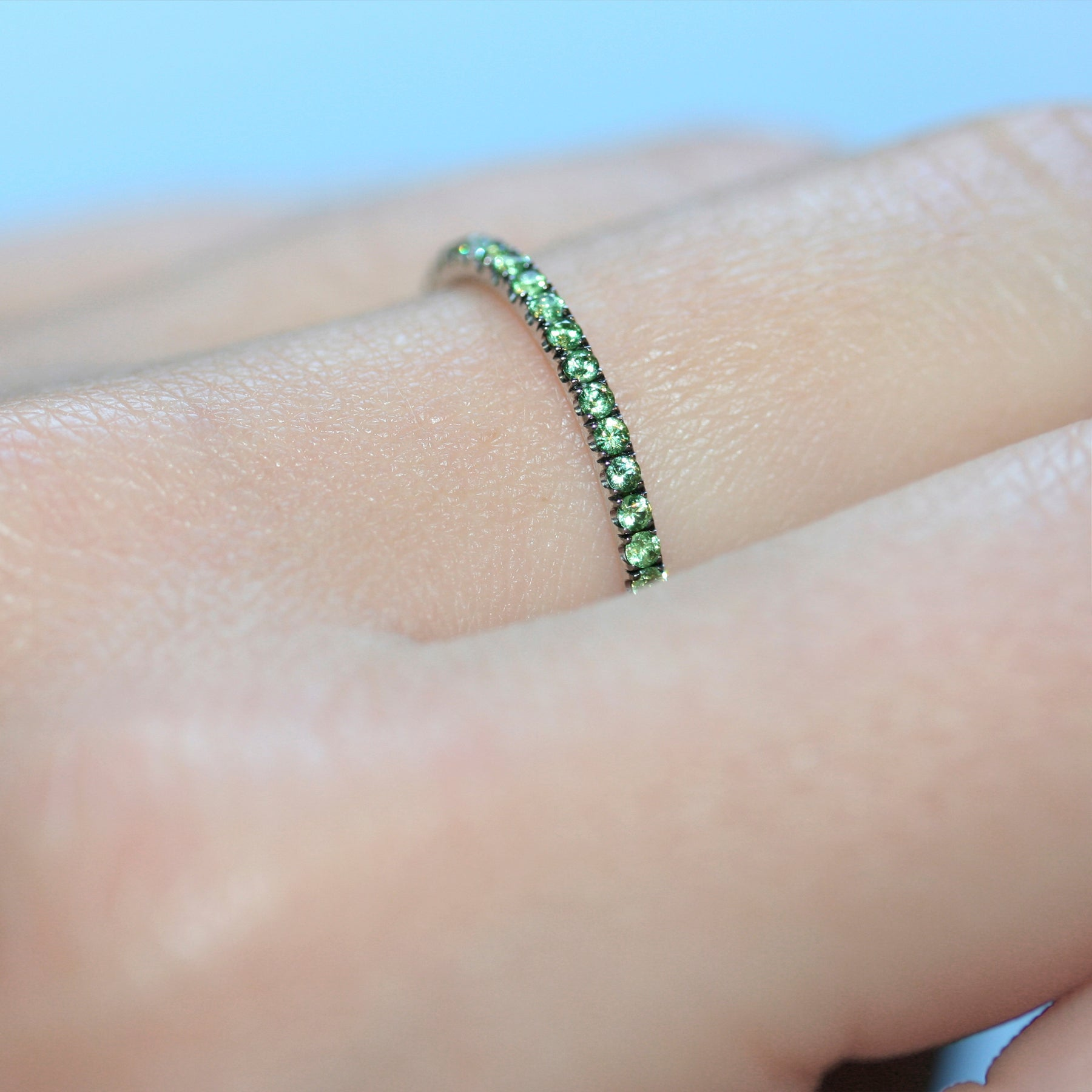 Closer shot of green garnet ring in 18ct white gold on a hand.