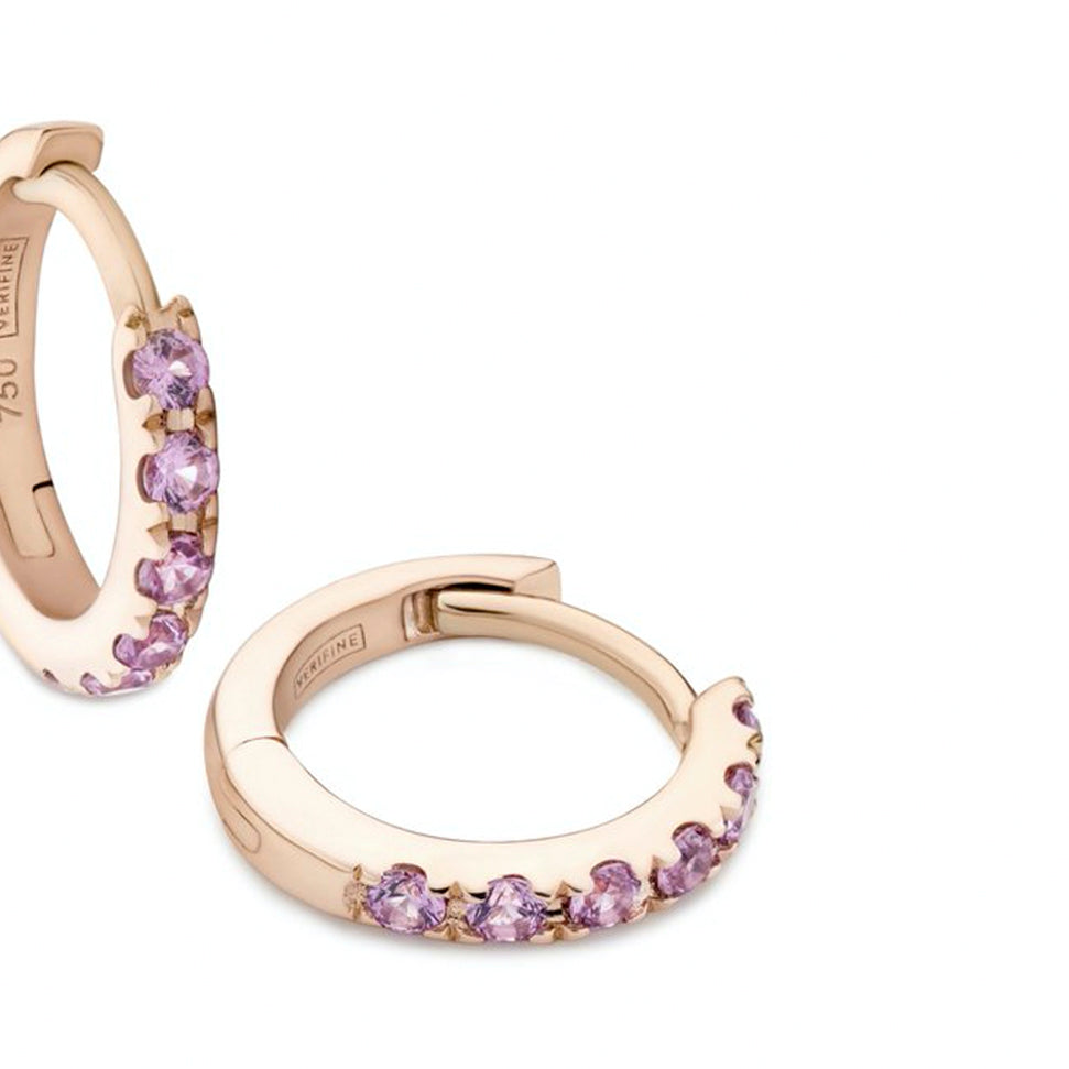 Close up of pink sapphire huggie earrings in 18ct rose gold on white background
