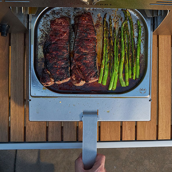 Steak and asparagus in drip tray drawer