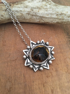 Amber set in sterling silver accented with sterlin silver hand stamped embelishments.  This amber pendant hangs on a 16 inch sterling silver chain.  Taylor Metal Designs.