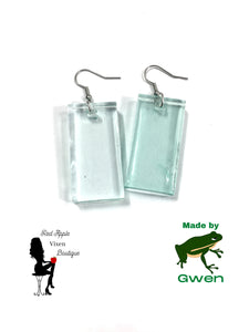 Light Blue Transparent rectangle shaped earrings. Made from Resin. Silver colored fish hook fasteners. Measures approximately 1.5 inches long and 1 inch wide.