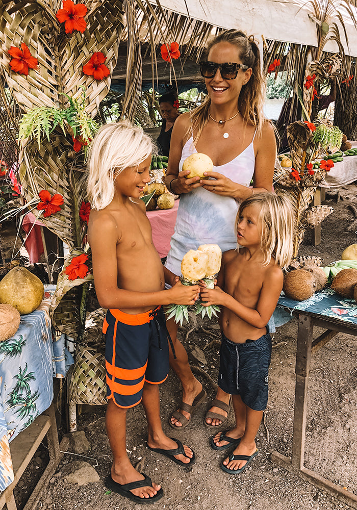Earthy Andy and her kids eating pineapple at the market
