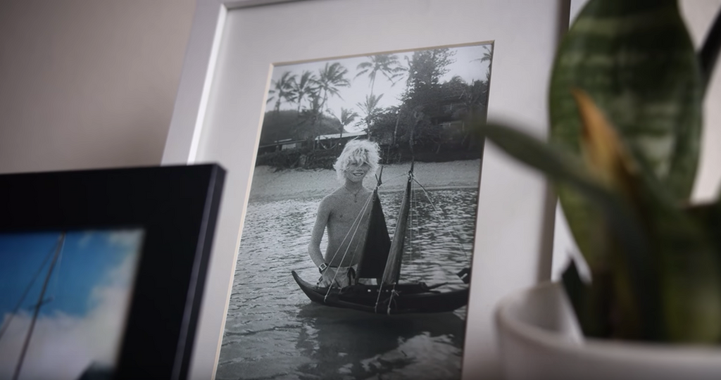 John John Florence stands in an old photo with a sailboat. Years before he partnered with Electric sunglasses, John had a dream to sail his boat to distant islands.