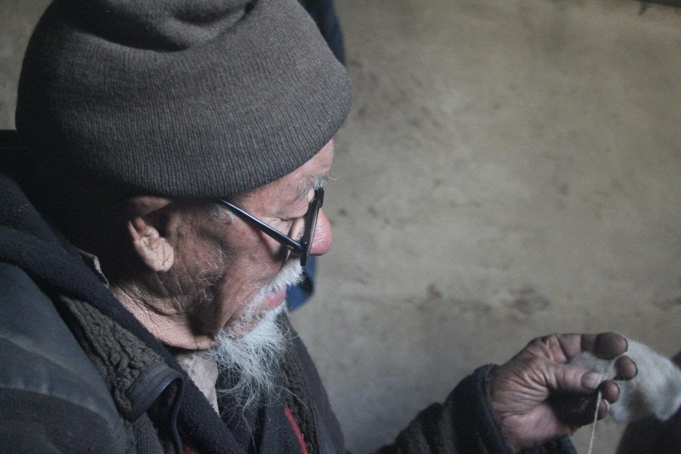 Old man hand-spinning at home in Kashmir