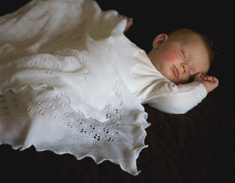sleeping baby beneath a christening shawl