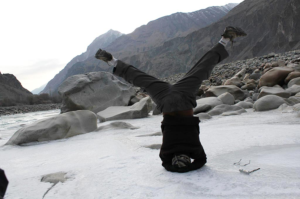 Atul performing a yogic headstand outdoors in the snow