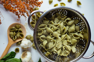 cooked flavored pasta in stainless steel strainer