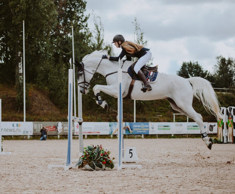 equestrian clothing girl riding on horse over horse jump