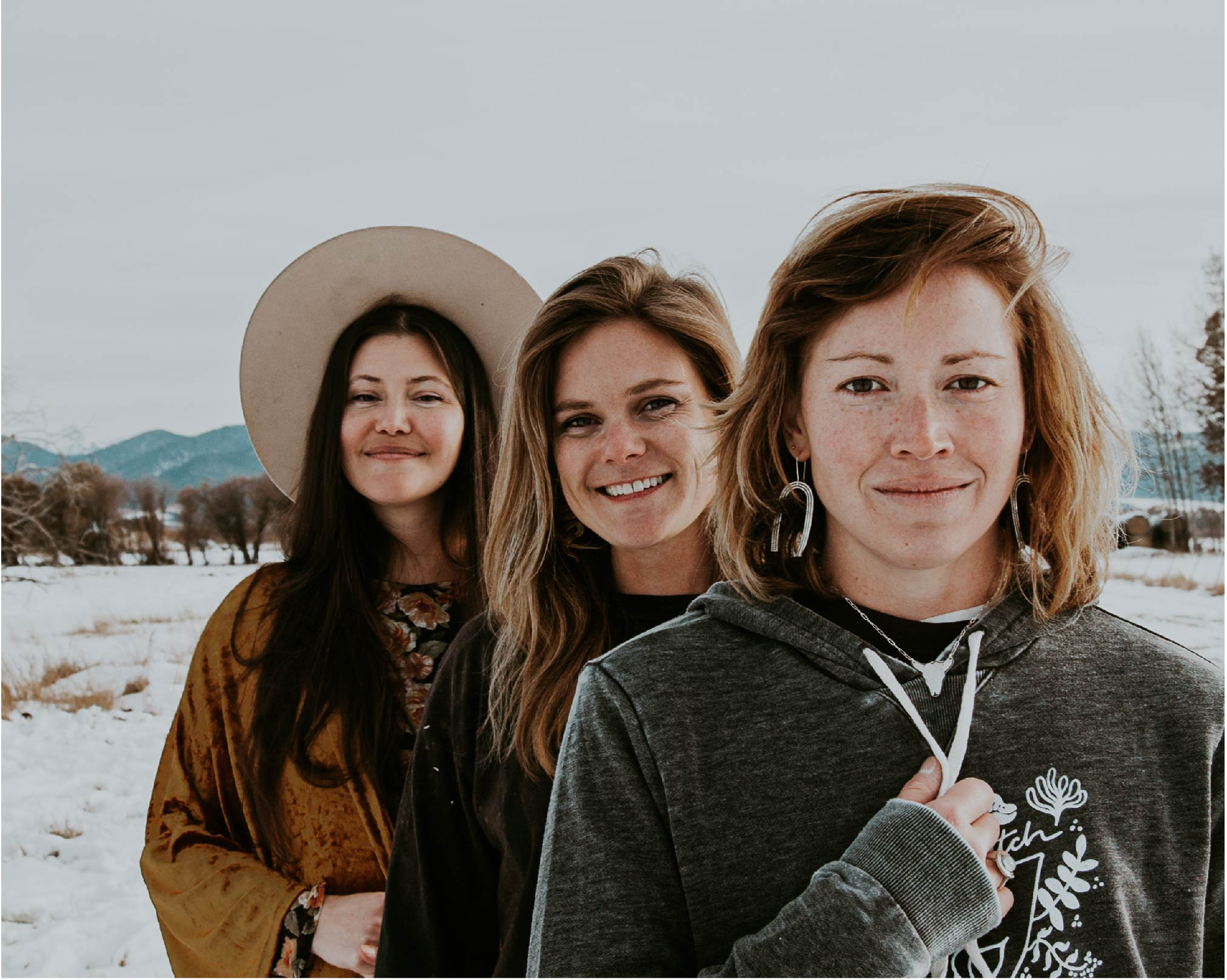 Three women standing in a snowy Bozeman, Montana field wearing Intrigue Ink shirts