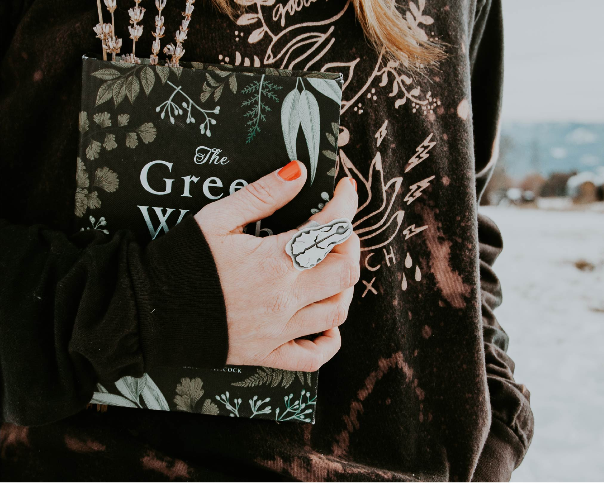 Woman holding a Green Witch book wearing a cow skull ring and a screen-printed pullover