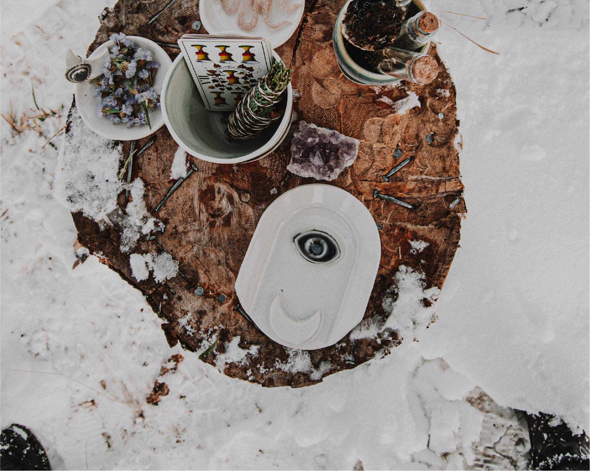 A setting of handmade ceramics, sage, and more witchy things on a snowy stump outside