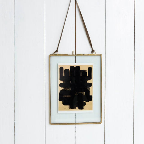 medium glass double sided picture frame with brass frame hanging on panelled wall with an abstract picture inside