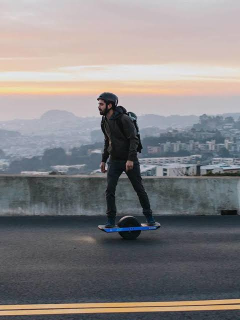 Riding a Onewheel XR into the sunset along the road