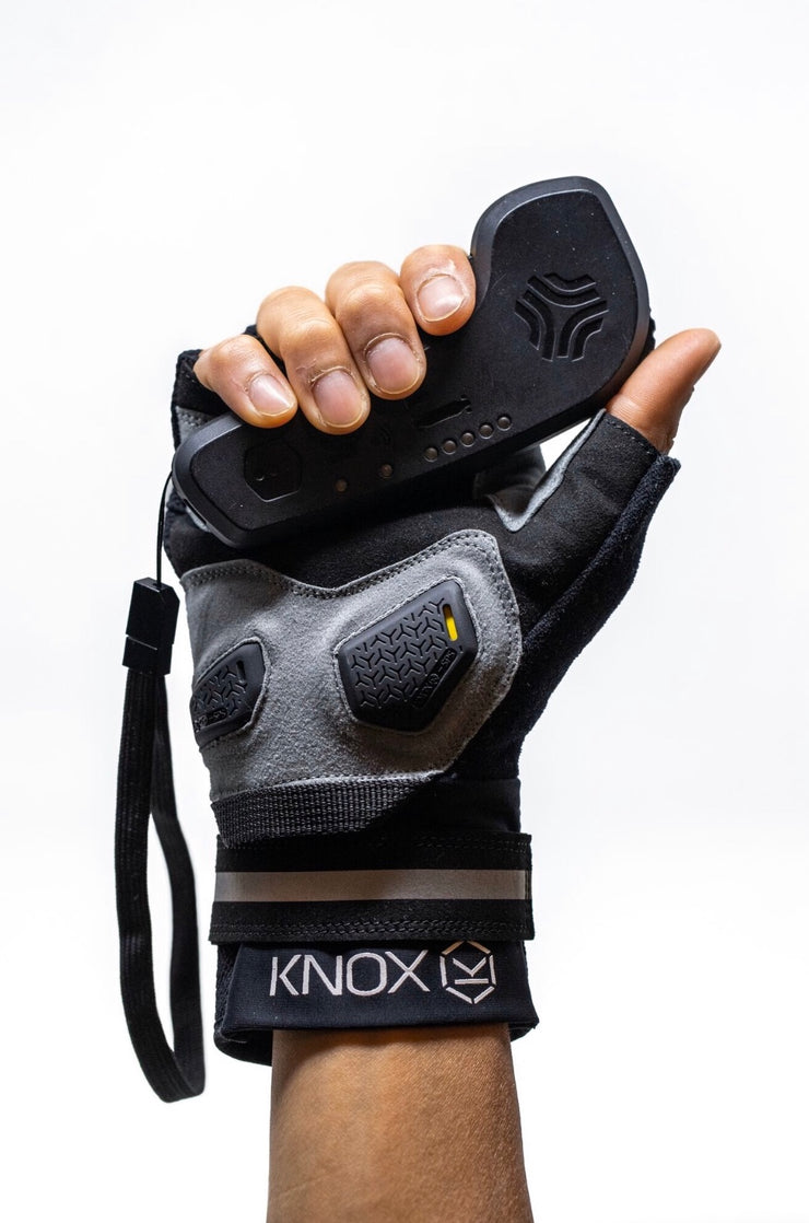 Front view of flatland fingerless glove holding a boosted remote plam side