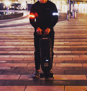 Man wearing halo lights on his arm ad holding a electric skateboard