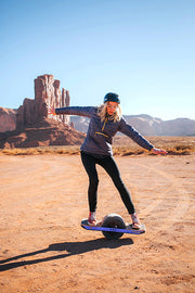 girl balancing on a onewheel in the desert