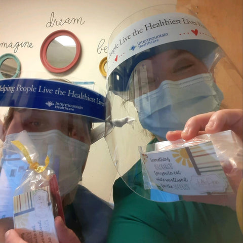 Two healthcare workers wearing PPE and holding treats from JulieAnn Caramels.