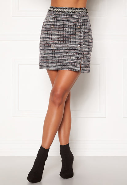 The Loren Skirt has a Tweed-like effect and has Black, White and red threads throughout.  The skirt has an attached frayed waist band and an invisible zip closure at the back. It is finished with silver button details and a peek-a-boo slit at the front. Stunning styled with a blouse, cami-top and worn with the matching Loren Jacket for a full suit look.
