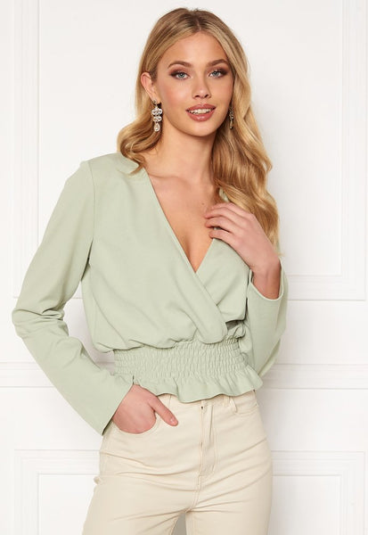 This is an image of the Sami Smock V Neck Blouse in Pistachio. This Lightweight Top is Jersey with a Stretchy Quality and wide sleeves.  It has a Short Length and Smocking at the hem.  A Perfect choice for every day as it is Simple and easy to wear.  Add some layered necklaces for a Boho feel and style this Blouse over some White Skinny Jeans.