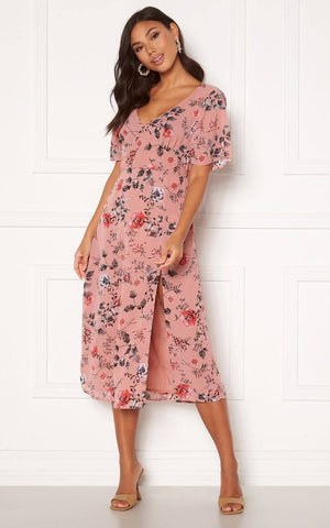 This is an image of the Ally Floral Print Flounce Midi Dress Dusty Rose. The Ally Flounce Dress is Ideal for Spring & Summer Occasions and has a real Vintage Style Silhouette that is Flirty and Flattering.  It has a V Neckline, Short Bell Sleeves and a Corset Cut under the Bust.  The back is Elasticated and has an Invisible Zip.  The Fabric is woven and non Stretch, It Flows nicely and there is a Slit at the side.