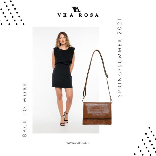 This is an image of our Jodie little black dress, It is a mini dress with capped sleeves and an overlay detail that enhances that hourglass shape at the waist, It is styled here with our Indie cross body handbag in brown