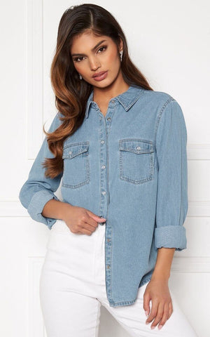 This is an Image of the Beatrice Shirt. This Everyday Shirt is Casual and can be worn closed or Open over a Tank Top, Cami or Dress.  It has Shiny White Buttons at the Front and on the Cuffs so that you have the option of rolling up the Sleeves.  It has Two Functional Front Pockets Finished with Buttons.  Denim is a Timeless Trend and this Versatile Blouse is definitely a piece worth investing in.   Fabric Composition: 100% Cotton