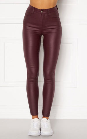 This is an image of the Bianca jeans. They are high waist and skinny fit with a button and zip closure at the front. They are a deep red/wine colour and have a coated effect giving them a wet look.