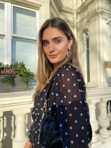 This is an image of Irish influencer and model Aoife Carty wearing out Abby Polka Dot Maxi Dress, Our gold hoop earrings and our Emily handbag