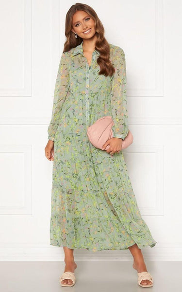 This is an image of the elsie green floral print tiered maxi dress. This Versatile Maxi Dress has Buttons From Top to Bottom, Has Long Sleeves  with a button on the cuffs and a Collar Detail.   It comes with a Stretchy, Light Green, Knee Length Slip Underneath it for Modesty and the Shell is Slightly Sheer with a Beautiful, Colourful Print all Over.  This dress is Perfect for any Summer Occasion and can be worn with Flat White Runners or Sandals during the day and transformed with heels and a chunky Belt for something more Dressy. Try Wearing it Open over a pair of Tight Jeans & a Cami.