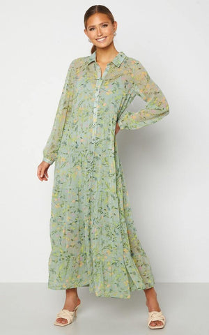 This is an image of the Elsie Floral Print Tiered Maxi Dress with Collar - Green. This Versatile Maxi Dress has Buttons From Top to Bottom, Has Long Sleeves  with a button on the cuffs and a Collar Detail.   It comes with a Stretchy, Light Green, Knee Length Slip Underneath it for Modesty and the Shell is Slightly Sheer with a Beautiful, Colourful Print all Over.  This dress is Perfect for any Summer Occasion and can be worn with Flat White Runners or Sandals during the day and transformed with heels and a chunky Belt for something more Dressy. Try Wearing it Open over a pair of Tight Jeans & a Cami.