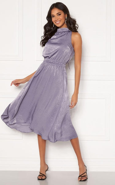 A Beautiful Dress for Occasions this Summer. This Silky Number is Light and Flowy with a Shimmer Effect.  This Dress has a High Neckline that ties at the back with a Keyhole Detail.    It has an Elasticated Overlay Detail at the waist which is Super Flattering and helps to achieve that Hourglass Shape.