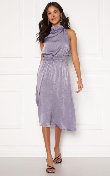 this is an image of The Emalie Halterneck Midi Dress in Lilac Shimmer. A Beautiful Dress for Occasions this Summer. This Silky Number is Light and Flowy with a Shimmer Effect.  This Dress has a High Neckline that ties at the back with a Keyhole Detail.    It has an Elasticated Overlay Detail at the waist which is Super Flattering and helps to achieve that Hourglass Shape.
