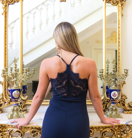 This is an image of the amelia lace black midi dress, it is Navy and midi length with a halter neckline. It has a delicate lace detail across the upper back and has a scalloped lace hem and a lace mesh slit.