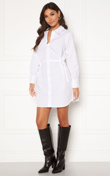 This is an image of the Lorina Cotton Shirt Dress in White. The Lorina is a fine Shirt Dress with Knot Details on the sides and Long Sleeves.  It is made out of a non-stretch, Woven Cotton fabric.  It has button closures the whole way up the front and the fit can be adjusted to your liking with the drawstrings on each side of the waist.  The Sleeve Length can also be adjusted as it has button closures on the cuff.  100% Cotton
