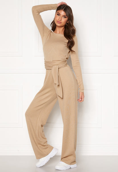 This is an image of the Maya Knitted Jumpsuit in Beige. It has long sleeves, a V at the upper back and has long flowy pants and a thick knitted belt attached which can be tied in different ways.