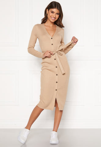 This is an image of the Nina Knitted Cardigan Dress. It is midi length with button closures up the front from centre bottom to top. It has long sleeves, a V neckline and an attached thin belt in the same fabric as the dress which can be bowed at the front. It is beige in colour.