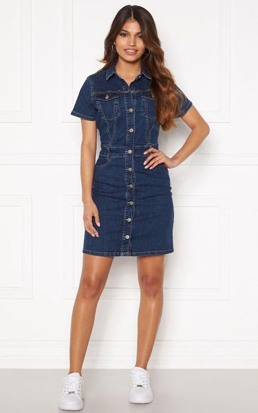 This is an Image of the Odina Dress. This Denim Dress is Figure Hugging and is made from a Stretchy Woven Fabric.   It has T-Shirt Length Sleeves and Silver Buttons closures the whole way up the front. It has functional Belt Loops & three pockets.  This is a great dress for Daywear because it's comfortable and works well with Flat White Runners, It can also be dressed up with Sandal Heels.