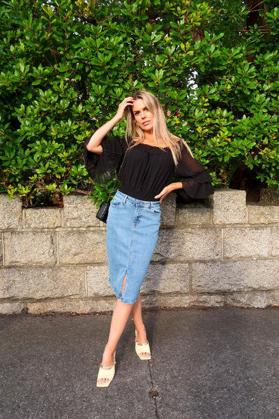 This is an image of influencer, presenter and Mom Rosalind Lipsett wearing our Madia Off the Shoulder blouse in black, our Elina Denim Skirt & Our Faith Quilted Handbag