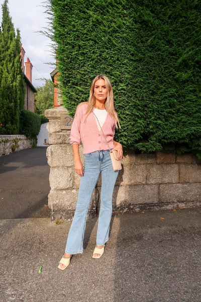 This is an image of Irish Influencer & Presenter Rosalind Lipsett wearing our Louisa Pink Cardigan, Our Tove Flares in light blue denim and our ruby quilted handbag in Nude