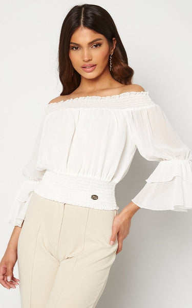 The Madia Blouse is off the Shoulder with Ruffle details on the Sleeves. It has Smocking Details on the Shoulders and at the Neckline.   It is Finished with a Branded Gold Emblem on the side of the waist. This Blouse is ideal for Styling with High Waisted Jeans or Leather Trousers.