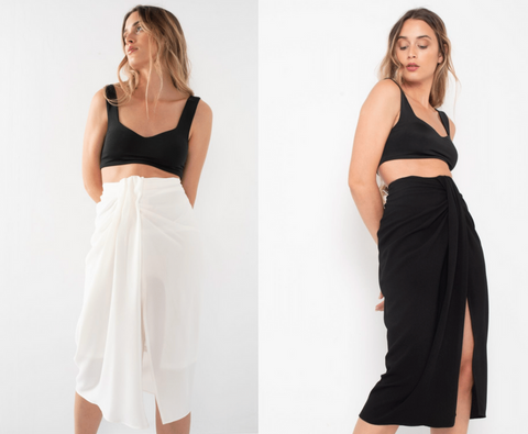 This is an Image of the Camila Midi Skirt in Black & in White. This Knotted Skirt is the Ultimate Wardrobe Staple for Spring/Summer.  It is midi length and fitted with an invisible zip at the back and a large knot detail on the tummy, making it ideal for hiding problem areas.  This Skirt can be worn Casually with Sandals and a Cropped Top, Or dressed up with a Blouse tucked in and some Heels.