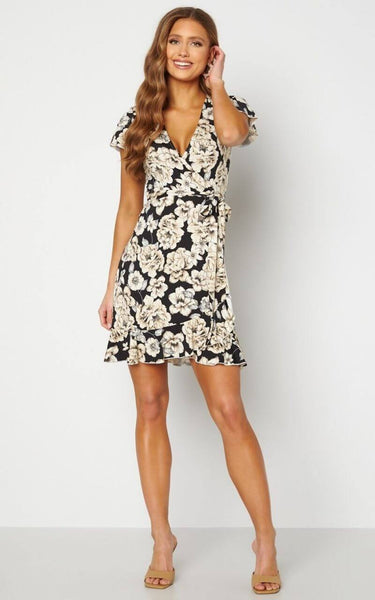 This is an image of the Sonnet Wrap Dress. This Feminine Wrap Dress is Mini Length with Short Frilly Sleeves.  It has a V Neckline and a Black & Cream Print Throughout.  The Hem is finished with a Frill and it has a Tie Closure at the Waist.  It is made of a Soft, Stretchy Fabric, Ideal for Summer days.