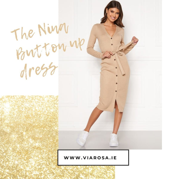 This is an image of the Nina Button up cardigan dress is Beige, it has a thin fabric belt attached to the waist which can be tied in a bow and is midi length with full length sleeves and brown buttons.