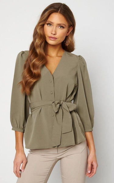 This is an Image of the Suzanne Blouse. This Blouse is Structured and has a Stunning Silhouette.  It has slight Volume in the Shoulders, Buttons down the front and the Sleeves are 3/4 Length.  It has a Tie Detail Attached to the waist which can be tied in a Bow and adjusted to cinch you in.  Ideal for Styling with Jeans & Leather Leggings or Trousers.