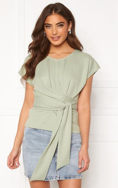 This is an image of the Tessa Tea Time Top in Pistachio. This Jersey Top is made of a Stretch Quality Fabric.  It has a High Neckline and a  Long Tie Detail attached to the waist which can be Wrapped around  Enhancing that Hourglass Shape.   This Top is a beautiful Shade of Pistachio Green that Looks Lovely Styled with White Jeans or Blue Denim for Summer.   It can be worn Casually or Dressed up for something a little more Formal.