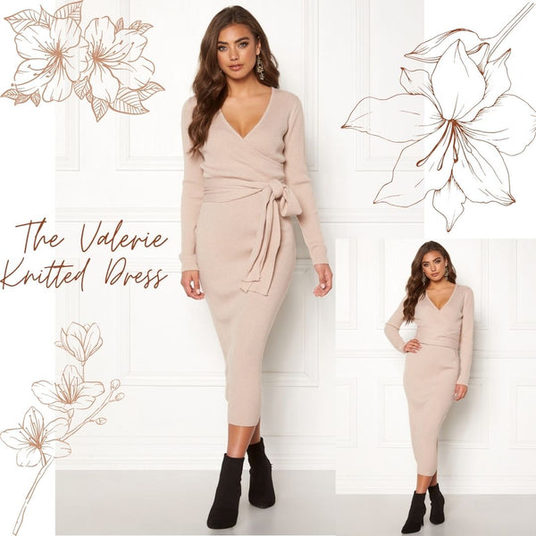 This is an image of the Valerie Knitted Midi Dress. It has Long Sleeves, A V neckline and is a light beige colour. It has a ribbed fabric and has a long fabric belt attached that can be bowed at the front or wrapped around the back. It is Styled here with black ankle boot heels.