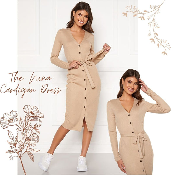 This is an image of our Nina Button Up Cardigan Dress in Beige. It is A Midi Length Knitted Dress with Long Sleeves and a ribbed fabric. It has a V neckline and Brown Button Closures up the front with a fabric belt attached that can be tied in a bow. It is styled here with white plain Runners but it can also be dressed up with a heel