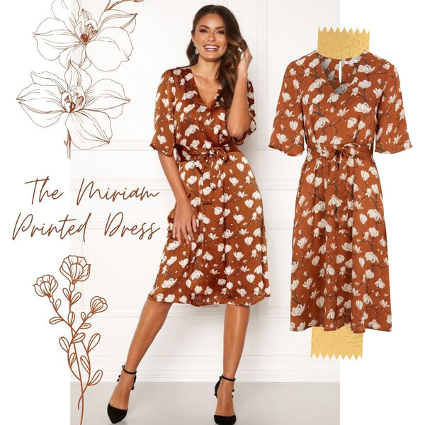 This is an image of the Miriam Vintage Style Printed Midi Dress. It is a Rusty red colour and has a White floral print all over. It has T shirt sleeves and is midi length with a V neckline. It is styled here with Black Pointed Court shoes