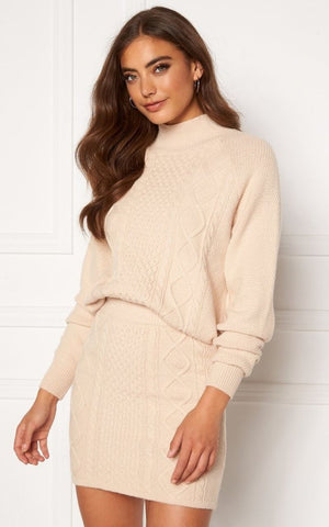 This is an image of the Aisha Knitted Polo neck which has a cable knit effect and the matching Aisha mini skirt. They are cream in colour.