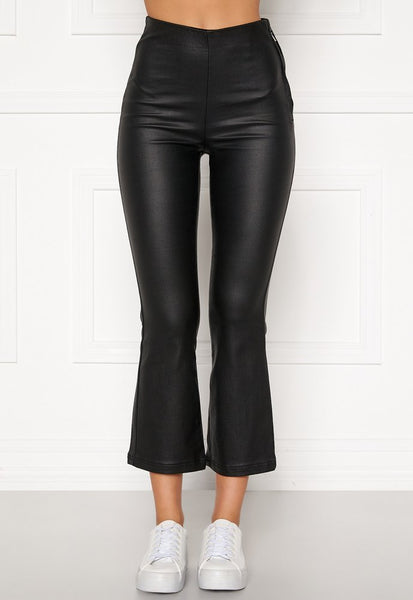 This is an Image of The Alicia Coated Kick Flare Trousers in Black. These Black, Coated Trousers are Cropped and are made of a Light, Stretchy fabric.  They have a Wet Look Effect.  They are tight fitting over the Bum and thighs and then more relaxed from the Knee down.  They are High Waist and have a hidden zip closure on the side.  These Trousers are easy to wear with either Sneakers or Heels.